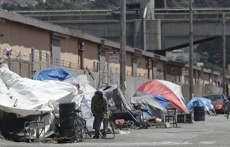 "In this file photo shows a man holding a bicycle tire outside of a tent along a street in San Francisco. Trump began a California visit on Tuesday, saying he will do ""something""