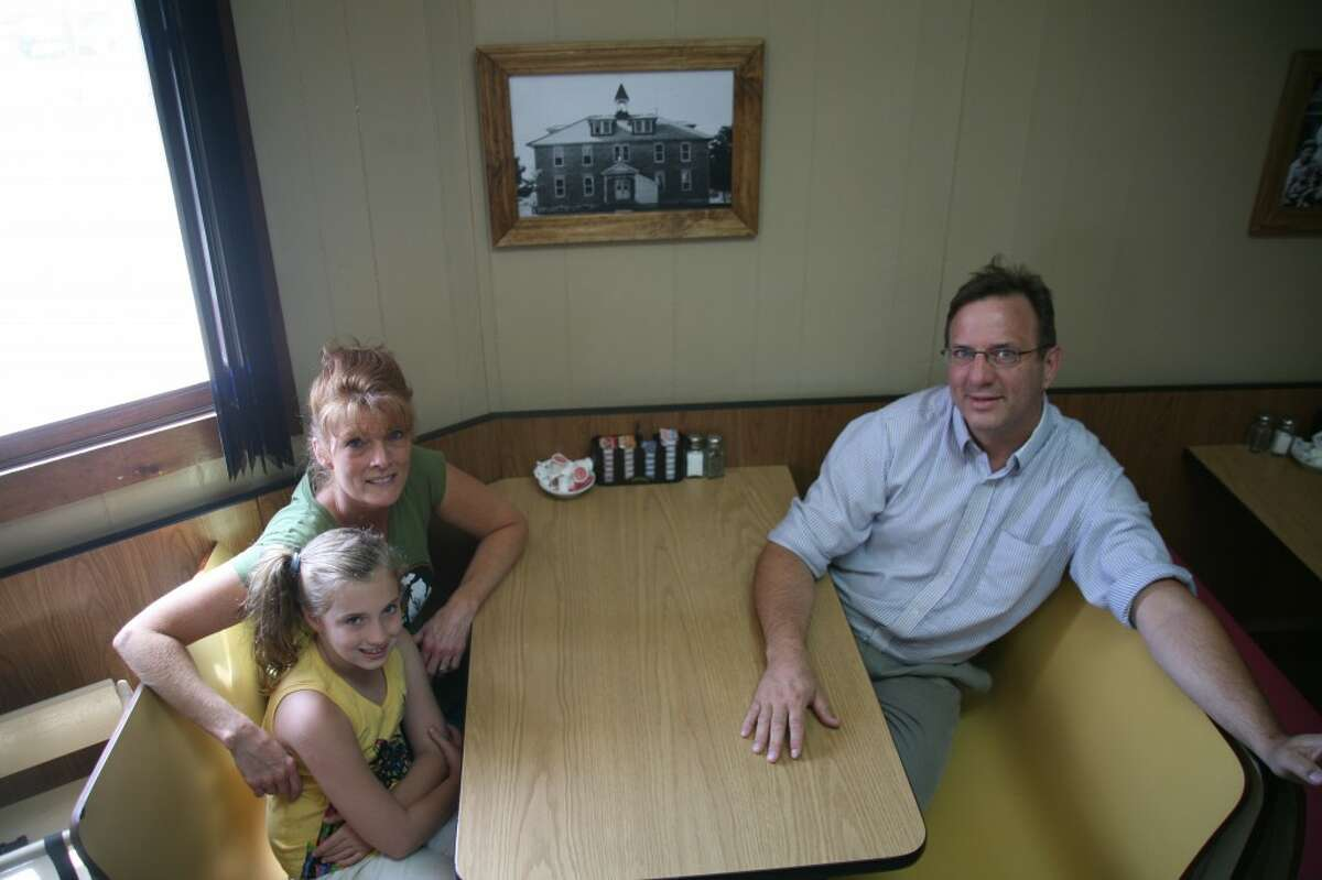 FAMILY OWNED: Owners Crystal and Matt Lotarski, along with their daughter Hailee, 7, sit in front of one of the many historical photos of Remus in the Wheatland Avenue Grill. Almost every booth features a photo from the community. (Pioneer photos/Eric Dresden)