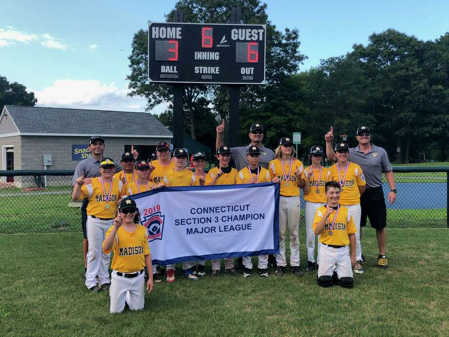 Members of the Madison Little League team hold up the championship banner after winning the Section 3 title on Wednesday. Photo: Will Aldam / Hearst Connecticut Media