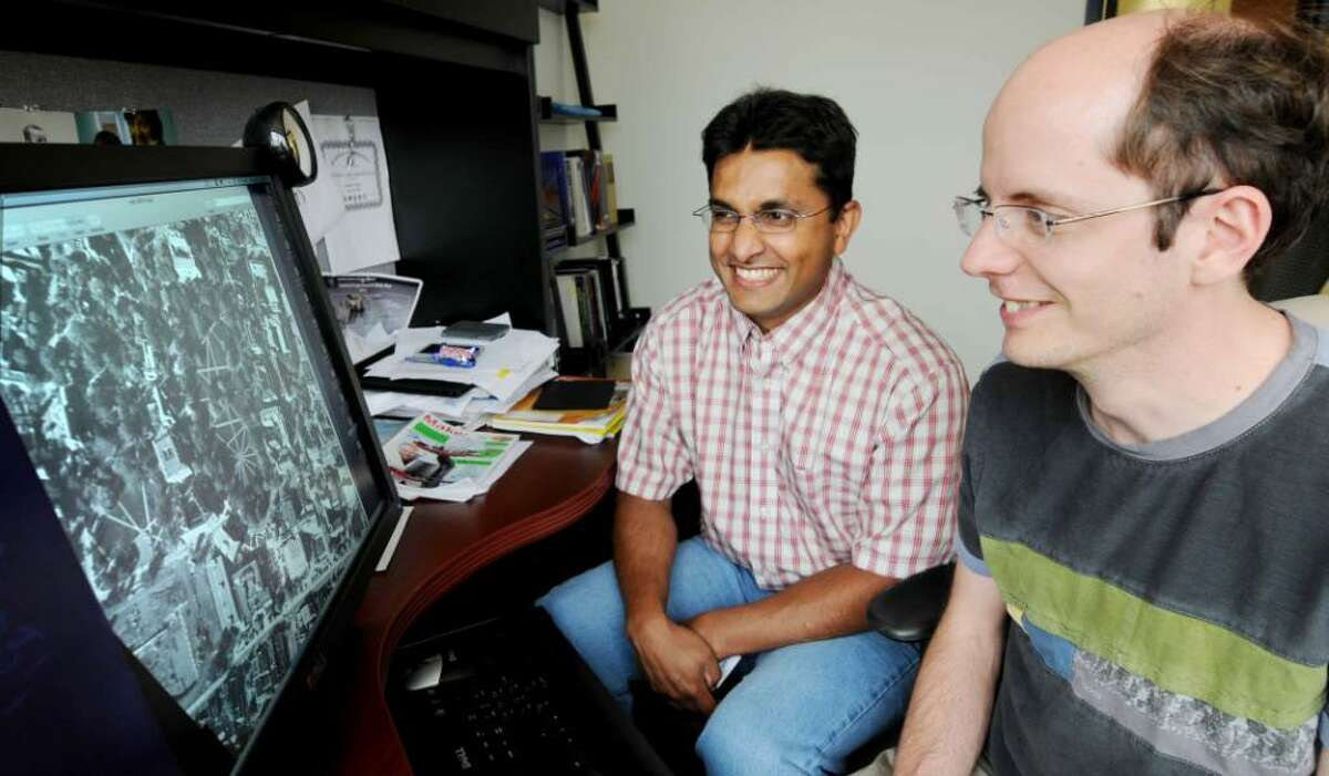 """Amitha Perera, left, a Technical Leader, and Roddy Collins, a Research & Development Engineer at Kitware Inc., view a frame of """"wide area"""" video from data gathered by aircraft. This is part of the research Kitware is currently conducting. Kitware is a local software firm that has just landed a $13.8 million contract with DARPA to develop a software system capable of automatically and interactively discovering actionable intelligence from wide area motion imagery of complex urban, suburban and rural environments. DARPA is the Defense Advanced Research Projects Agency that is funding the development of this wide-area motion imagery video technology to be used to identify and assess threats in such situations as battlefield environments. The researcher's colleagues, Dr. Anthony Hoogs, Director of Computer Vision, and Dr. Will Schroeder, Kitware CEO, were interviewed on the implications of the surveillance software in their Halfmoon company headquarters on Wednesday, July 21, 2010."""