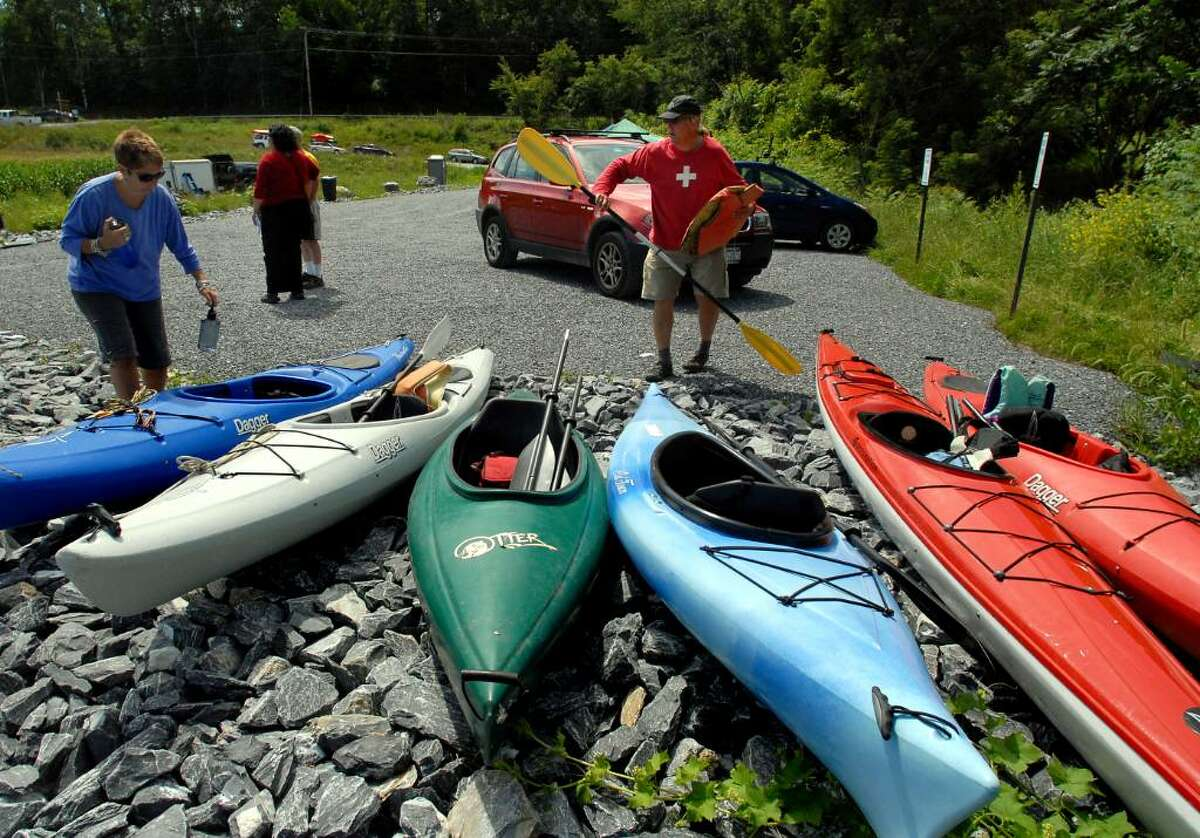 Paul Schroeder, volunteer coordinator of the Rensselaer Land Trust, right, and his wife, Beth, left, prepare to kayak from the newly dedicated Hoosic River Public Boat Launch on Saturday, on the Hoosic River in Hoosick. (Cindy Schultz / Times Union