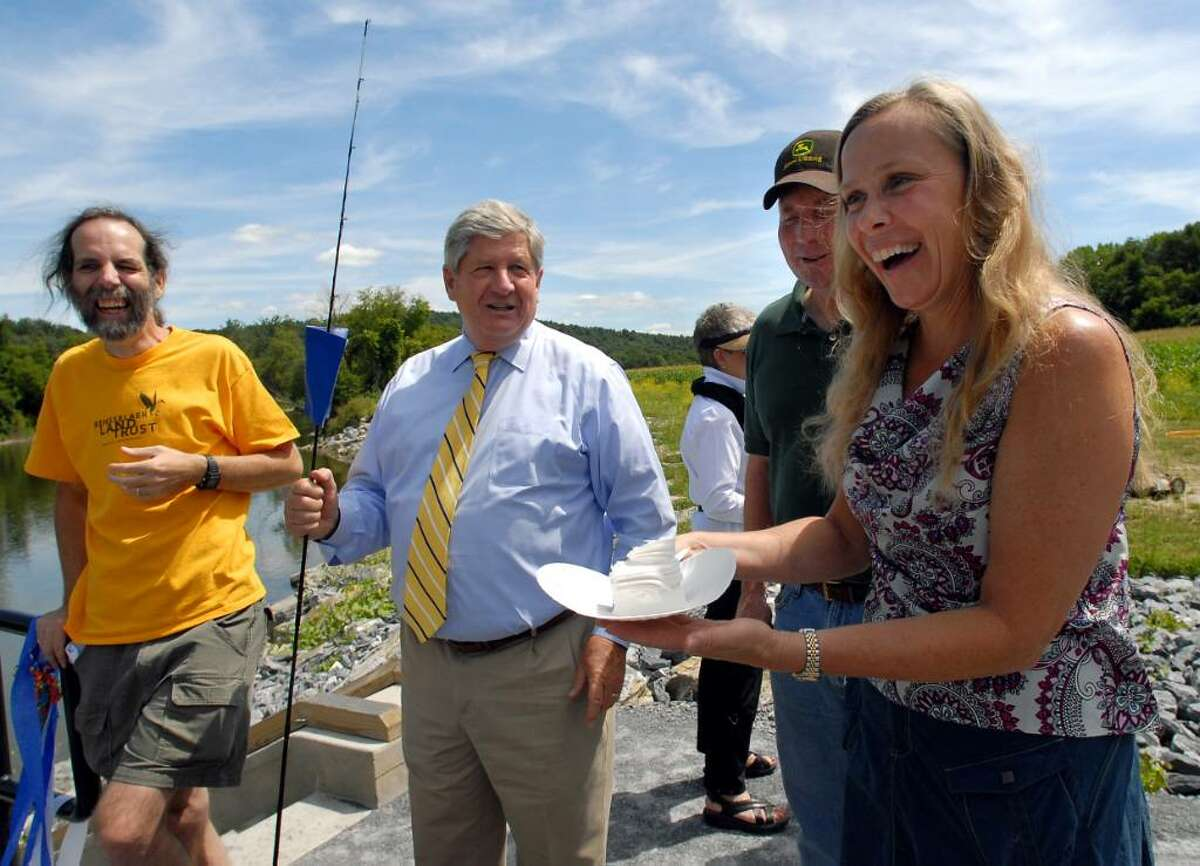 Christine Young, executive director of the Rensselaer Land Trust, right, offers cake as Nick Conrad, president, left, talks with Sen. Roy McDonald, second from left, and Jeff Wysocki, town of Hoosick councilman, during the dedication of the Hoosic River Public Boat Launch on Saturday on the Hoosic River. (Cindy Schultz / Times Union)