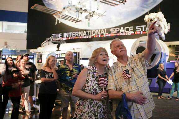 John and Wendy Largen of Seabrook, Texas, watch as footage of the Apollo splash down is shown at Space Center Houston on Wednesday, July 24, 2019.
