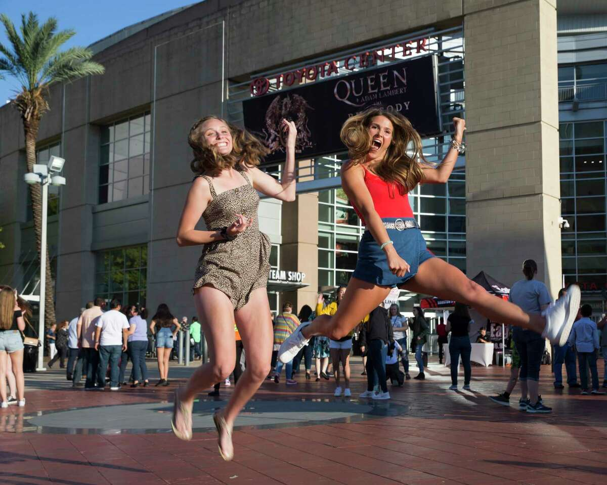 Emma Keiser, left, and Ainsley Cunningham jump in the air to take a photograph before the Queen + Adam Lambert: The Rhapsody Tour concert at Toyota Center on Wednesday, July 24, 2019, in Houston.