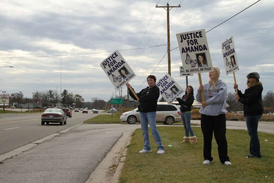 PROTEST: Tammy Vonrosen, left, and Vicki Lankey, in grey, hold protest signs with friends on Nov. 7 outside of Big Daddy's 24-Hour Towing, located on Northland Drive south of Quality Inn and Suites. The group picketed outside the business, which employed Cecil Wallis Sr., a suspect in the 2004 murder of Vicki Lankey's daughter, Amanda. Wallis committed suicide three days later. (Pioneer photos/ Jon Eppley)