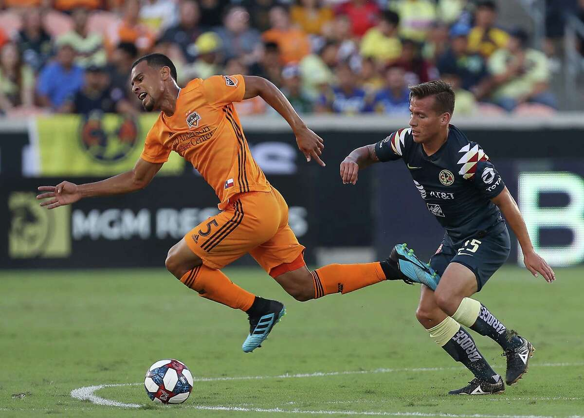 Houston Dynamo midfielder Juan David Cabezas (5) is tripped up by Club América midfielder Pedro Arce (15) during the first half of a of the Leagues Cup match at BBVA Stadium on Wednesday, July 24, 2019, in Houston.