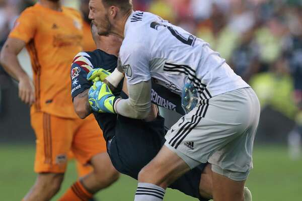 Houston Dynamo goalkeeper Joe Willis (23) has the wind knocked out of him after a collision with Club América Fernando González during the first half of a of the Leagues Cup match at BBVA Stadium on Wednesday, July 24, 2019, in Houston.