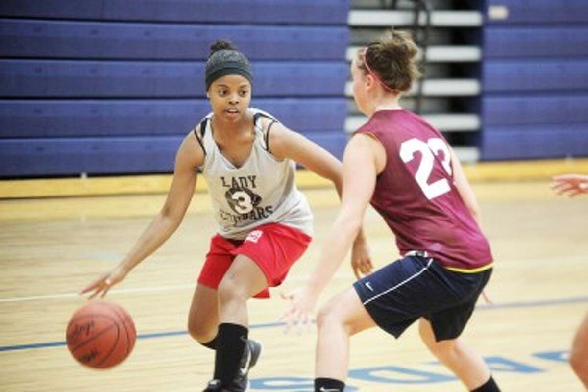 READY TO DRIVE: Crossroads Charter Academy guard Kaela Brooks looks to drive the lane against a Marion defender during a scrimmage on Thursday. Brooks is one of four returning players for the Cougars this season. (Pioneer photo/Martin Slagter)