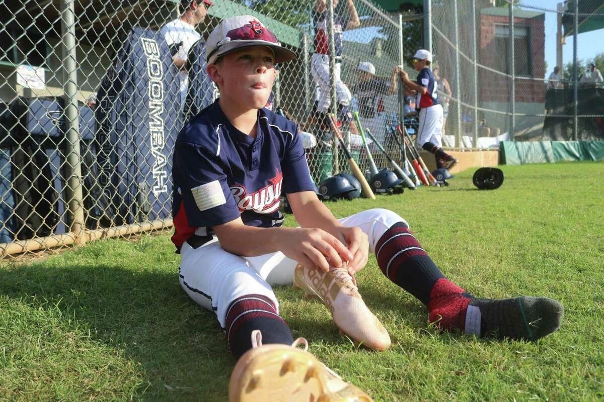 Wilson Reagan watches the West End All-Stars get their 10-minutes of practice in as he puts on his cleats prior to Tuesday night's game in Tyler.