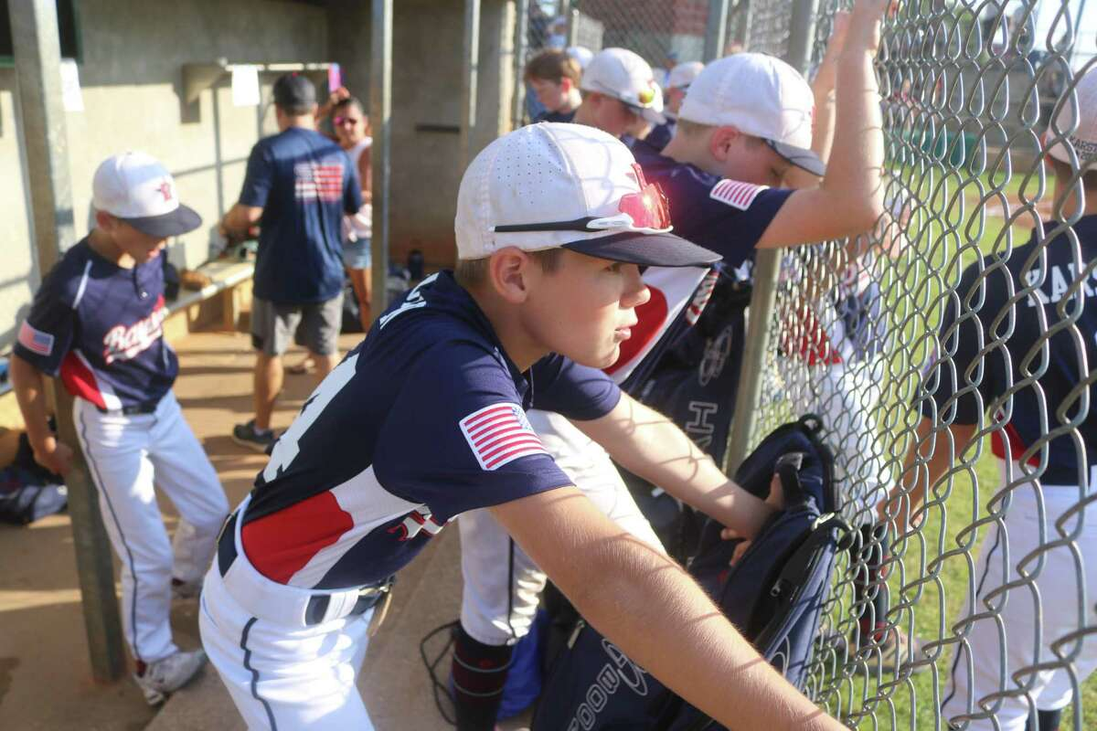 Koehl Morgan peers through the fence, concentrating on the West End All-Stars and their 10 minutes of warm-up time Tuesday night in Tyler.