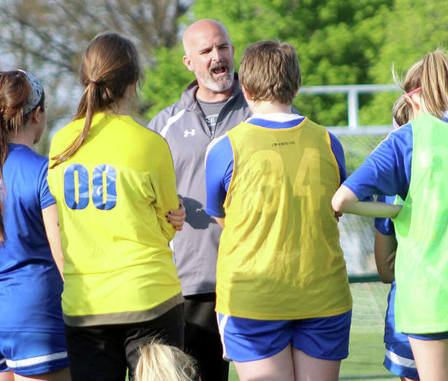 Marquette girls soccer coach Brian Hoener talks to his team at halftime of a late-season win over Belleville East. Marquette went 10-2 the second half of the season and captured the championship of its own Class 1A regional tournament. Photo: Pete Hayes | The Telegraph