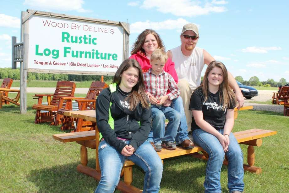 RUSTIC HOME DESIGN: Wood By Delines owners Lewis and Summer offer a variety of rustic log furniture for both indoor and outdoor use. The business is located on the corner of U.S. 10 and 170th Ave. in Hersey. Here, the Delines sit with their children (from left) Olivia, Torigan and Talon. (Pioneer photo/Karin Armbruster)