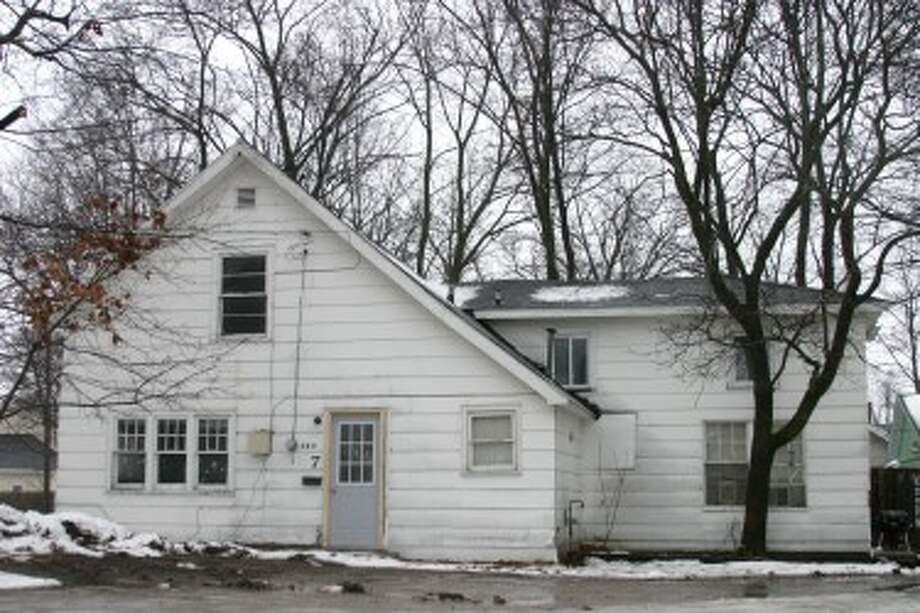 RAIDED: Five people were arrested for running a meth lab at one of the homes located at 324 S. State St., pictured above. The owner of the property said it is set for foreclosure next month.