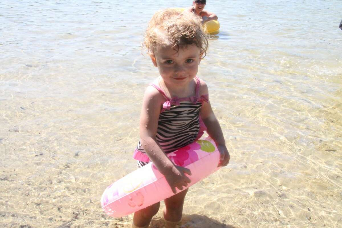 LAKE DAY: Amelia Jo Matzen, 1, takes a break from the lake while her mother Nina looks on. Nina said Amelia Jo was nervous to be in the water at first, but once she got in, she loved it. Amelia Jo, Nina, Terri Tucker and other family members were enjoying a day at School Section Lake together.