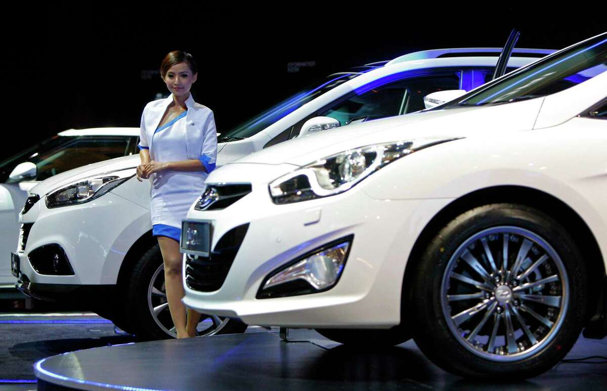 FILE - In this Sunday, Nov. 16, 2013, file photo, a model poses next to a Hyundai Tucson facelift on display at the Kuala Lumpur International Motor Show in Kuala Lumpur, Malaysia, In 2014, Hyundai says it will starts selling Tucson SUV powered by a hydrogen fuel cell. It will be the first mass-market vehicle of its type to be sold or leased in the U.S. (AP Photo/Lai Seng Sin, File)