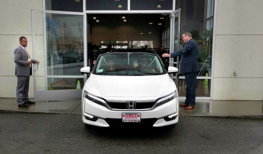 Alex Akrami, (left) sales manager and Jim Baily, general manager wave goodbye to passenger, Heather Mc Laughlin, of San Ramon, as she takes delivery of its first of its kind hydrogen fuel-cell cars the Honda Clarity, at Dublin Honda on Monday Feb. 6, 2017, in Dublin, Ca. Mark Burda, the Clarity brand ambassador drives the vehicle. Photo: Michael Macor, Staff / The Chronicle / ONLINE_YES