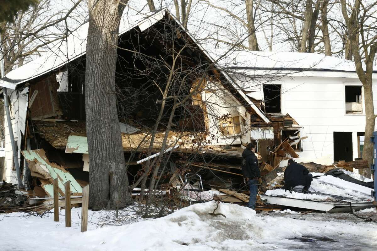 DEMOLITION: Demolition crews worked on Monday to tear down one of the houses located at 324 S. State Street in Big Rapids. The small, white house was the site of a methamphetamine investigation in 2012, but now has new owners. (Pioneer photo/Whitney Gronski-Buffa)