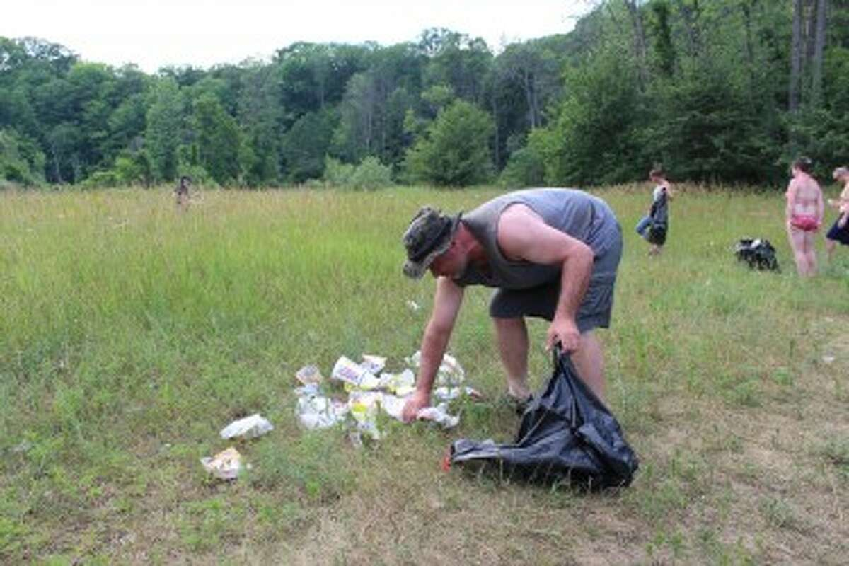 TRASHY PIT STOP: Dawg Tags Tattoo owner Dennis Cook cleans up garbage along the Muskegon River east of Ferris. The area is a regular stop for people tubing down the river. It is also a popular party spot for college students in the area. (Pioneer photos/Lonnie Allen)