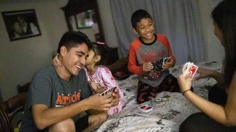 Jose Escobar, Carmen Escobar, Walter Escobar, and Rose Escobar play Uno before going to bed.