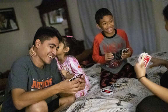Jose Escobar, Carmen Escobar, Walter Escobar, and Rose Escobar play Uno before going to bed.