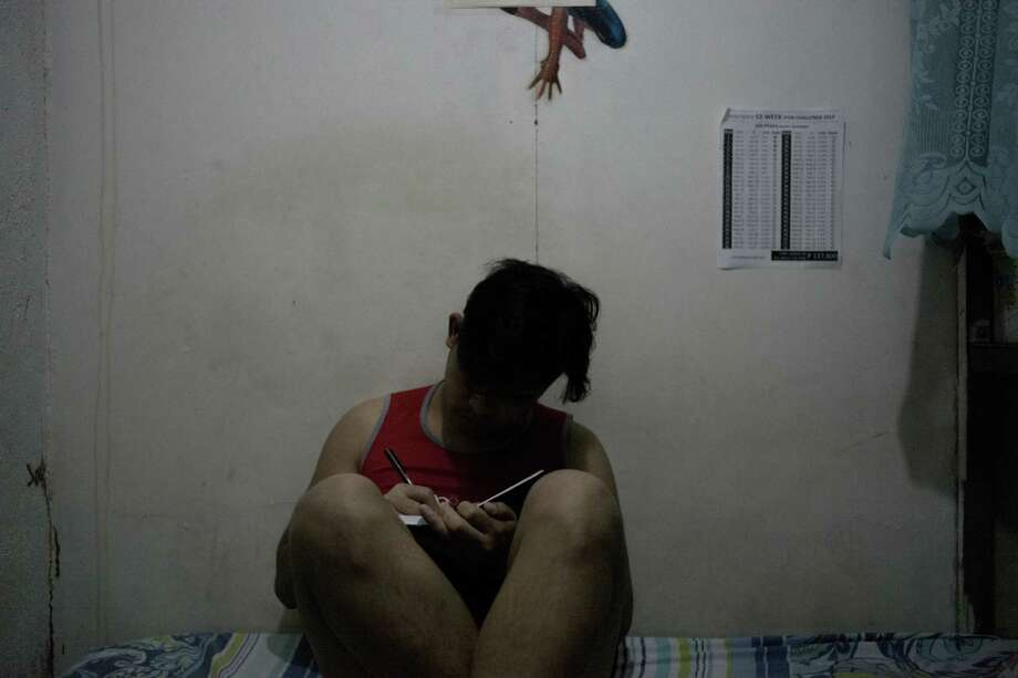 Lester, whose last name isn't being used, sits on his bed, jotting down notes. He works as a content moderator in the Philippines, which has caused emotional distress for him. Photo: Photo For The Washington Post Carlo Gabuco / Carlo Gabuco