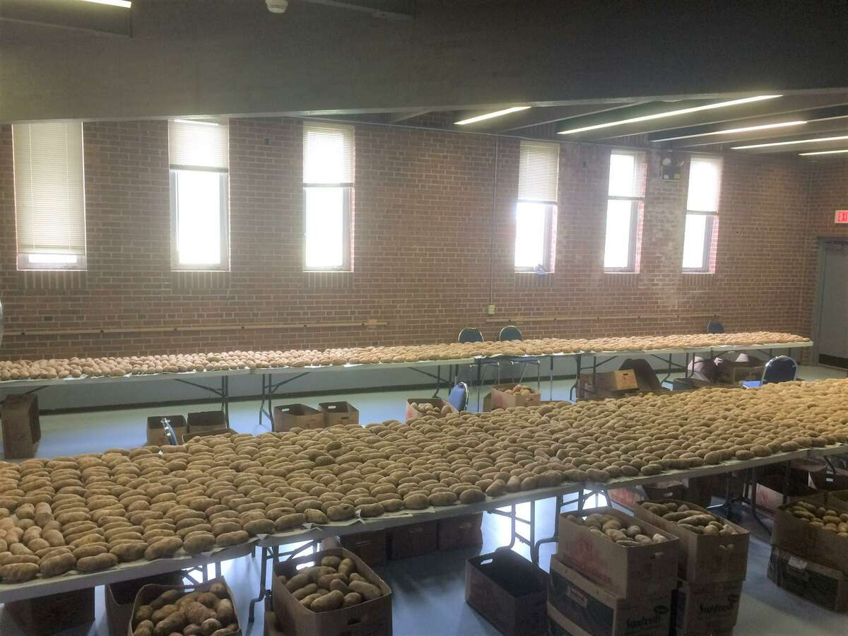 Tables of potatoes await prep at the festival.