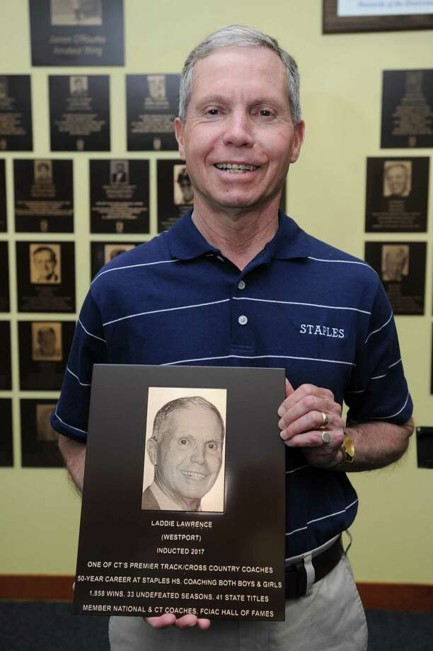 Longtime Staples High School coach Laddie Lawrence poses for a photo with his plaque during the unveiling ceremony for the 2017 inductees into the Fairfield County Hall of Fame inside UConn Stamford in downtown Stamford, Conn. on Thursday, May 10, 2018. Lawrence has led the cross country, indoor and outdoor track and field teams at Staples since 1970 and has accumulated 1,824 wins and 146 career championships. Photo: Michael Cummo / Hearst Connecticut Media / Stamford Advocate