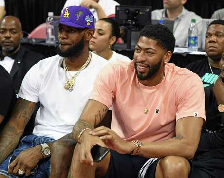 LAS VEGAS, NEVADA - JULY 05:  NBA players LeBron James (L) and Anthony Davis watch a game between the New Orleans Pelicans and the New York Knicks during the 2019 NBA Summer League at the Thomas & Mack Center on July 5, 2019 in Las Vegas, Nevada. NOTE TO USER: User expressly acknowledges and agrees that, by downloading and or using this photograph, User is consenting to the terms and conditions of the Getty Images License Agreement.