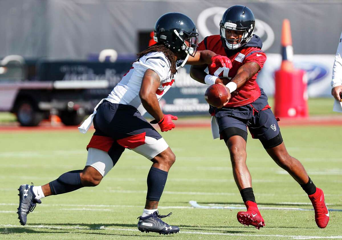 Houston Texans running back D'Onta Foreman (27) takes a handoff from quarterback Deshaun Watson (4) during training camp at the Methodist Training Center on Thursday, July 25, 2019, in Houston.