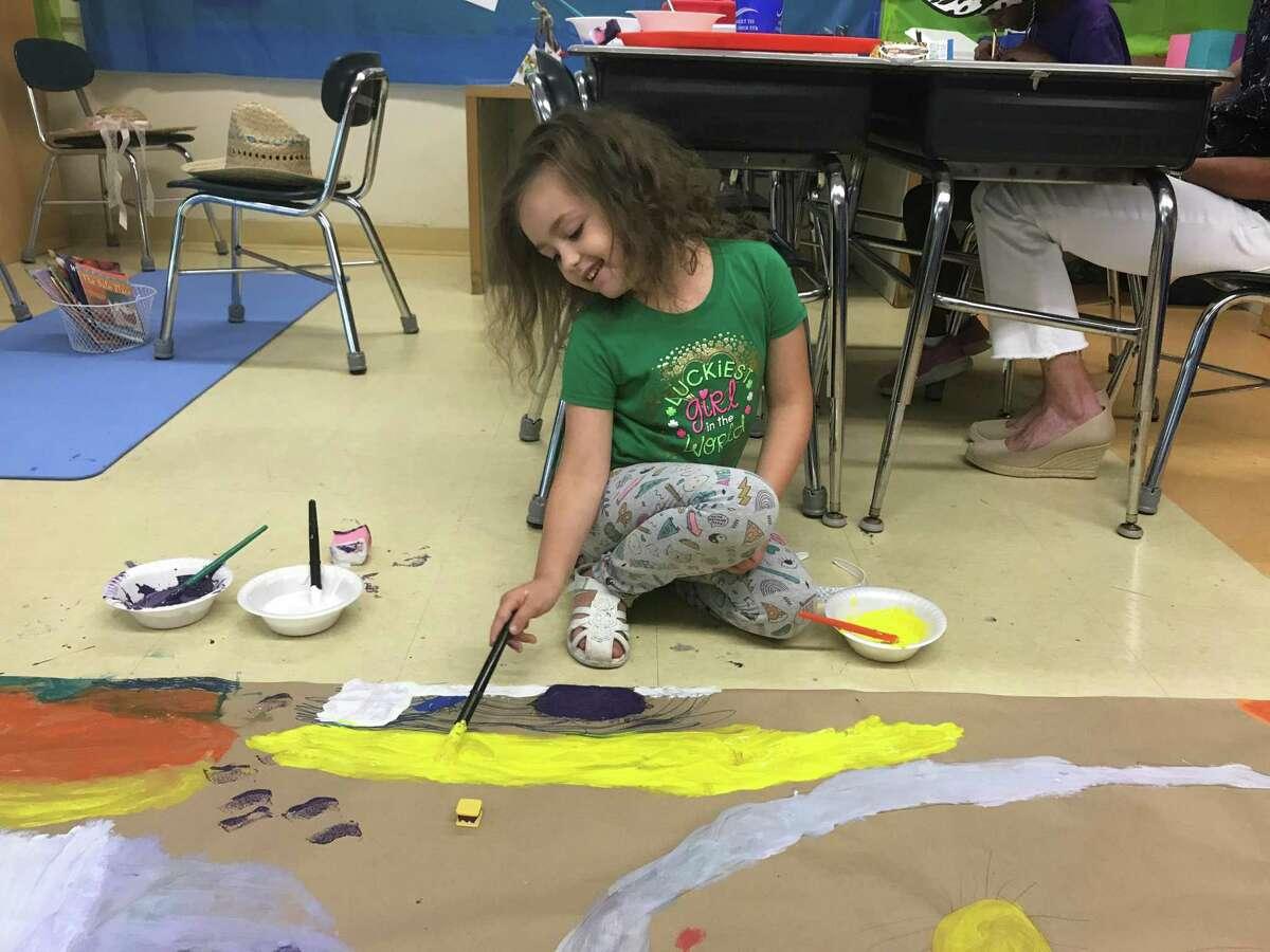 Makaela Martinez, 6, uses yellow paint to add sand to a seascape on July 24, 2019.