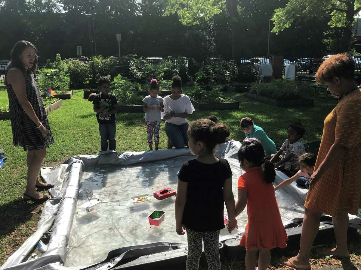 Students at a play-based summer learning program at Conte West Hills School float boats made of plastic containers on July 24, 2019.
