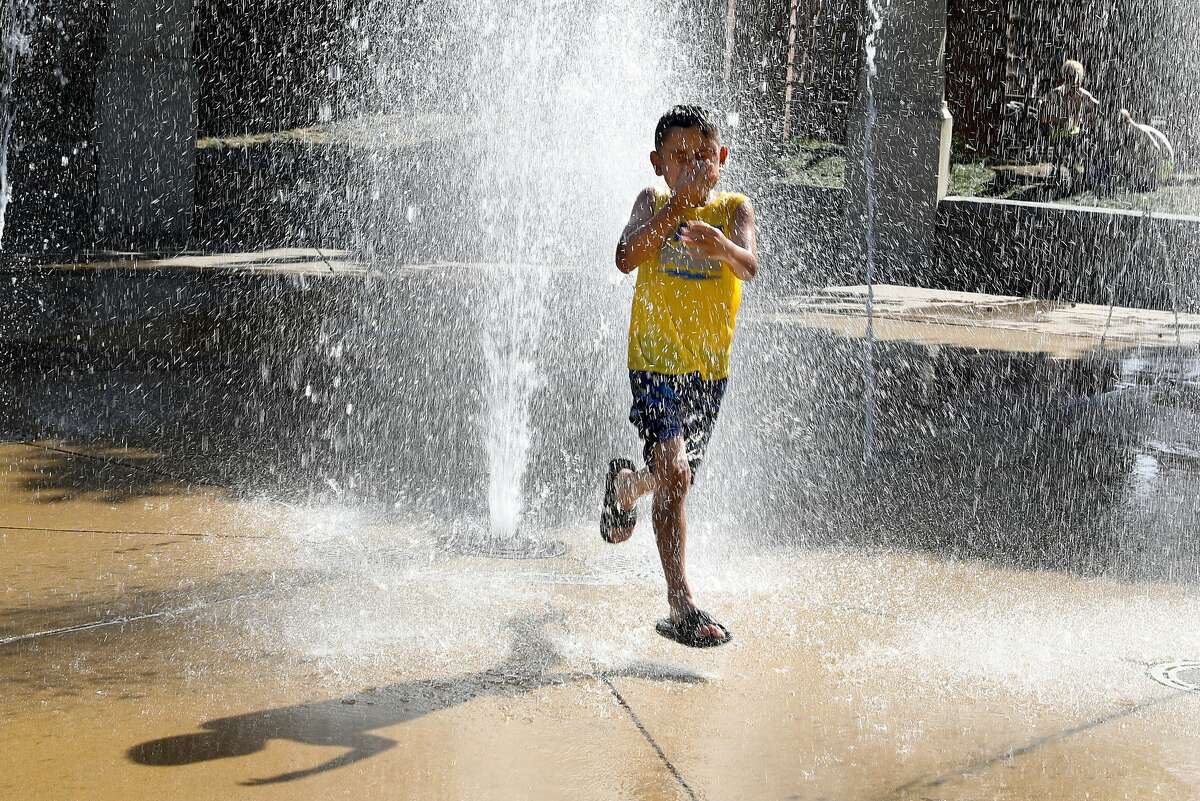 Iker Zaizar, 7 years old, from Livermore walks through a fountain at Flag Pole plaza to cool off during temperatures reaching 102 degrees in downtown Livermore on Monday, June 10, 2019 in Livermore, Calif.