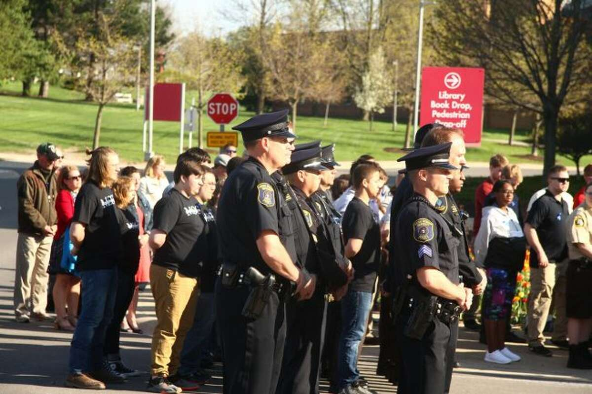 Police officers stand together and listen to speakers during the Police Memorial Ceremony.