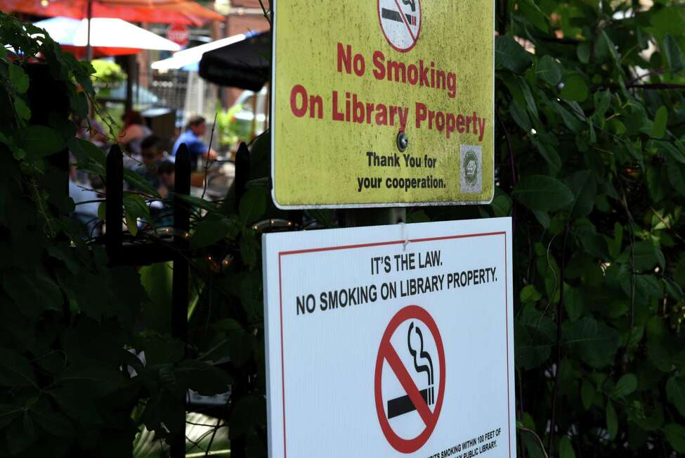 No smoking signs are placed around the parking lot at Saratoga Springs Public Library, which is adjacent to several bars on Thursday, July 25, 2019, in Saratoga Springs, N.Y. A new smoking restriction could play havoc on the library, which is smack dab in the middle of multiple bars. (Will Waldron/Times Union)