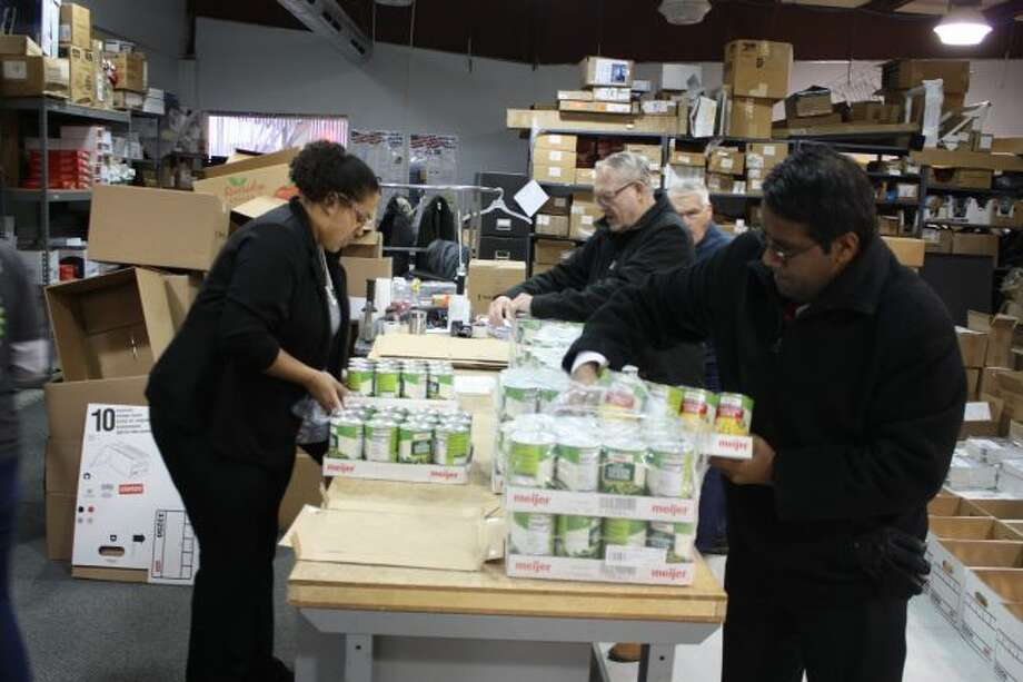 Rotary Club of Big Rapids members help sort foodstuffs at the the Great Lakes Book and Supply warehouse on Clark Street Wednesday before packing them in boxes. (Pioneer photo/Tim Rath)