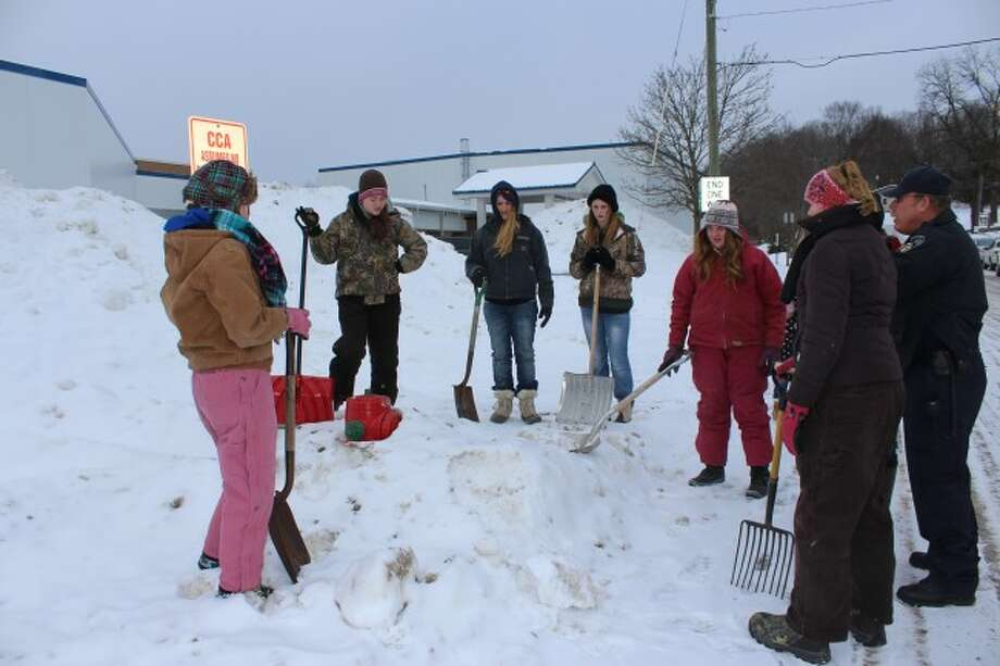 DIGGING OUT: Area 4-H Club helps Big Rapids Department of Public Safety firefighters clear snow away from fire hydrants on Thursday.