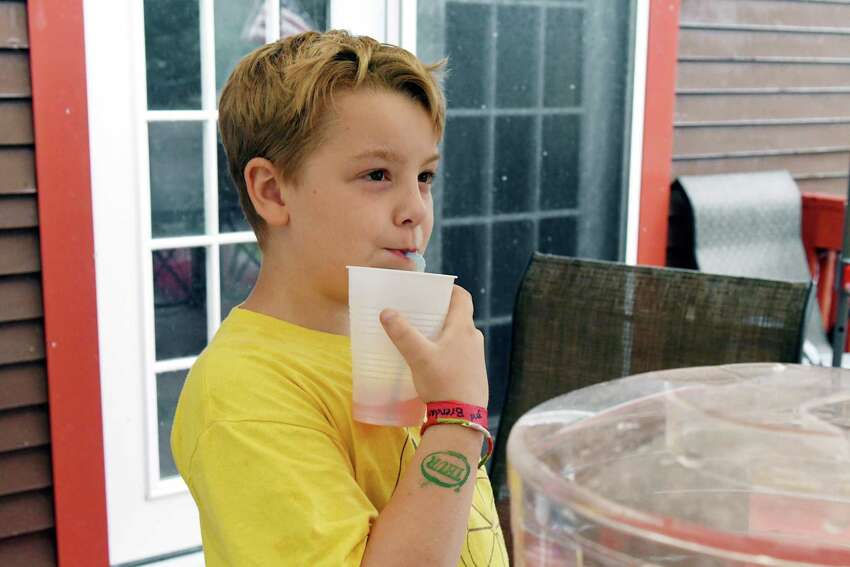 Brendan Mulvaney, 8, drinks a glass of his pink lemonade in front of his lemonade stand on Thursday, July 25, 2019 in Ballston Spa, N.Y. Brendan's Lemonade stand will be open outside of Saratoga County fairgrounds until Sunday. (Catherine Rafferty/Times Union)