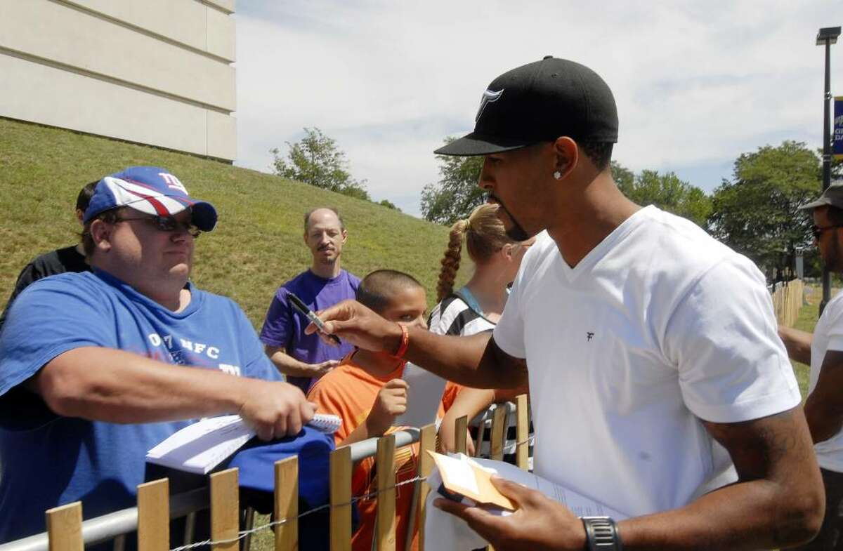 The Giants' Terrell Thomas, right, signs an autograph for Jim Labombard of Watervliet as players arrive at training camp in Albany. (AP Photo/Hans Pennink)