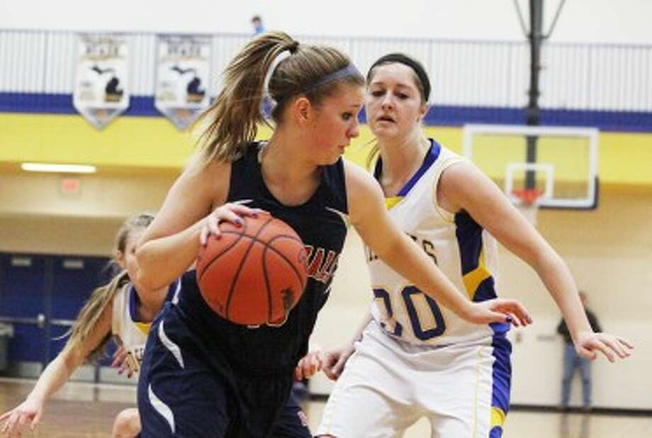 DRIVING BY: Big Rapids' Kasey Woodworth looks to get past Morley Stanwood's Kayla Rosman during Friday's high school basketball action. (Pioneer photo/Bob Allan)