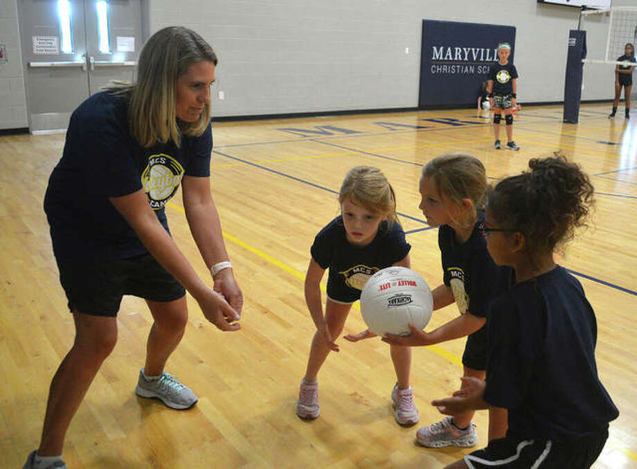 Maryville Christian School girls' volleyball coach Jill Harrison works with some young players during a volleyball camp at MCS on Thursday. Photo: Scott Marion/The Intelligencer