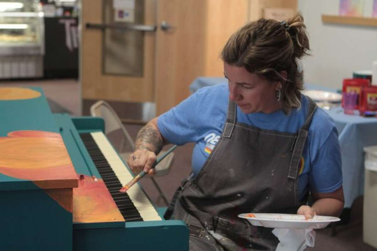 Artist Amber Prout paints poppies on a piano for the