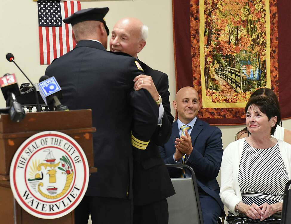 Michael Geraci Sr. hugs his son and new Watervliet Police Chief Anthony Geraci, left, after he was sworn in to the department at the Watervliet Senior Center on Thursday, July 25, 2019 in Watervliet, N.Y. Anthony's mother Mary sits at right. Anthony Geraci retired from the Albany Police Department where he was a lieutenant to accept the appointment. (Lori Van Buren/Times Union)
