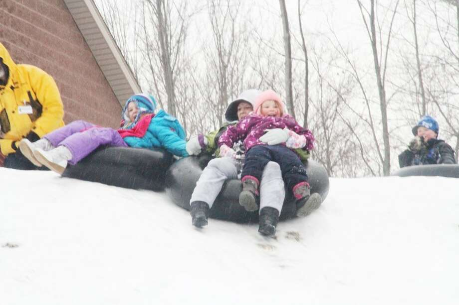 TUBING: Elizabeth McDonald tubes down a hill at Cran-Hill Ranch with her daughter, Desiree Mead, at left, and her neice, Sophia Oliver, at right. Event-goers could tube down three hills at Winterfest on Sunday.