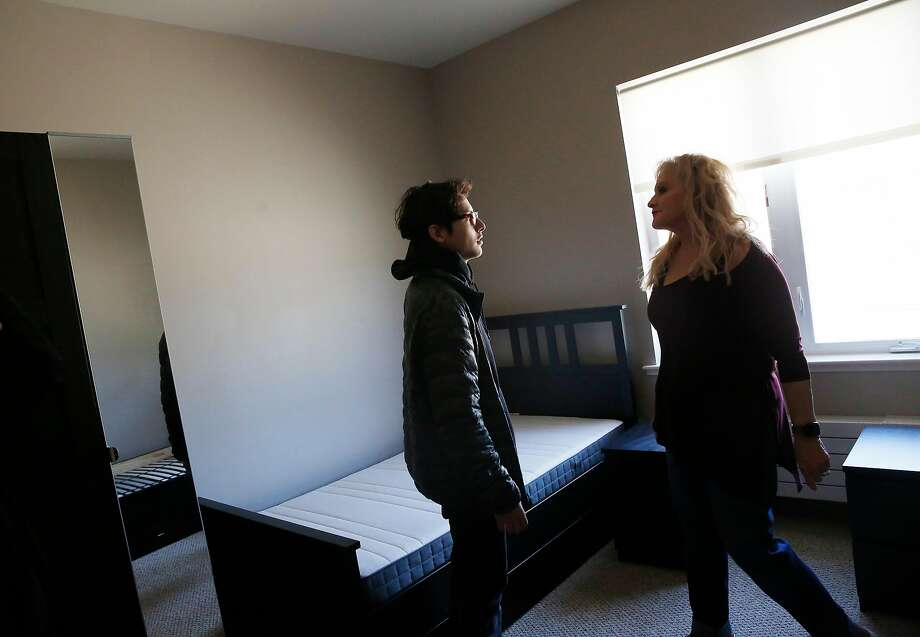 Abisai Aguilar, 15, talks with Teri Delane, executive director, as he looks over a dorm room at Life Learning Academy. Photo: Lea Suzuki / The Chronicle