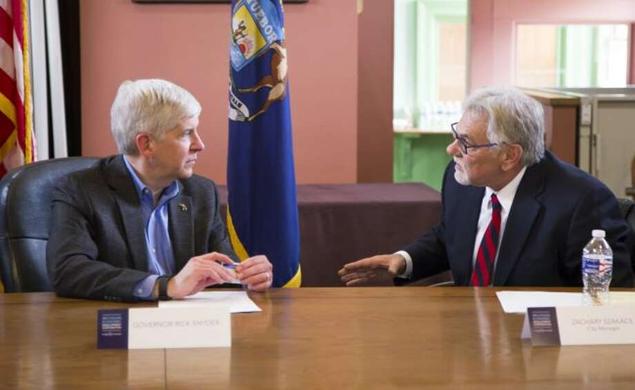 Evart City Manager Zack Szakacs (right) speaks with Gov. Rick Snyder regarding problem areas within Evart such as a lack of transportation for residents to travel to jobs, blight, poor rental property conditions and more during the Rising Tide meeting in April 2016. Snyder is expected to congratulate officials with Evart's graduation from the program on Wednesday, Sept. 5. (Pioneer file photo)