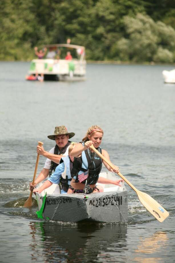 """CARDBOARD BOAT: Joel Nichols (at stern) captains the """"S.S. Let it Float"""" cardboard boat during Saturday's Damsel in Distress Rescue competition. The event was part of the inaugural Dam Festival in Rogers Heights."""