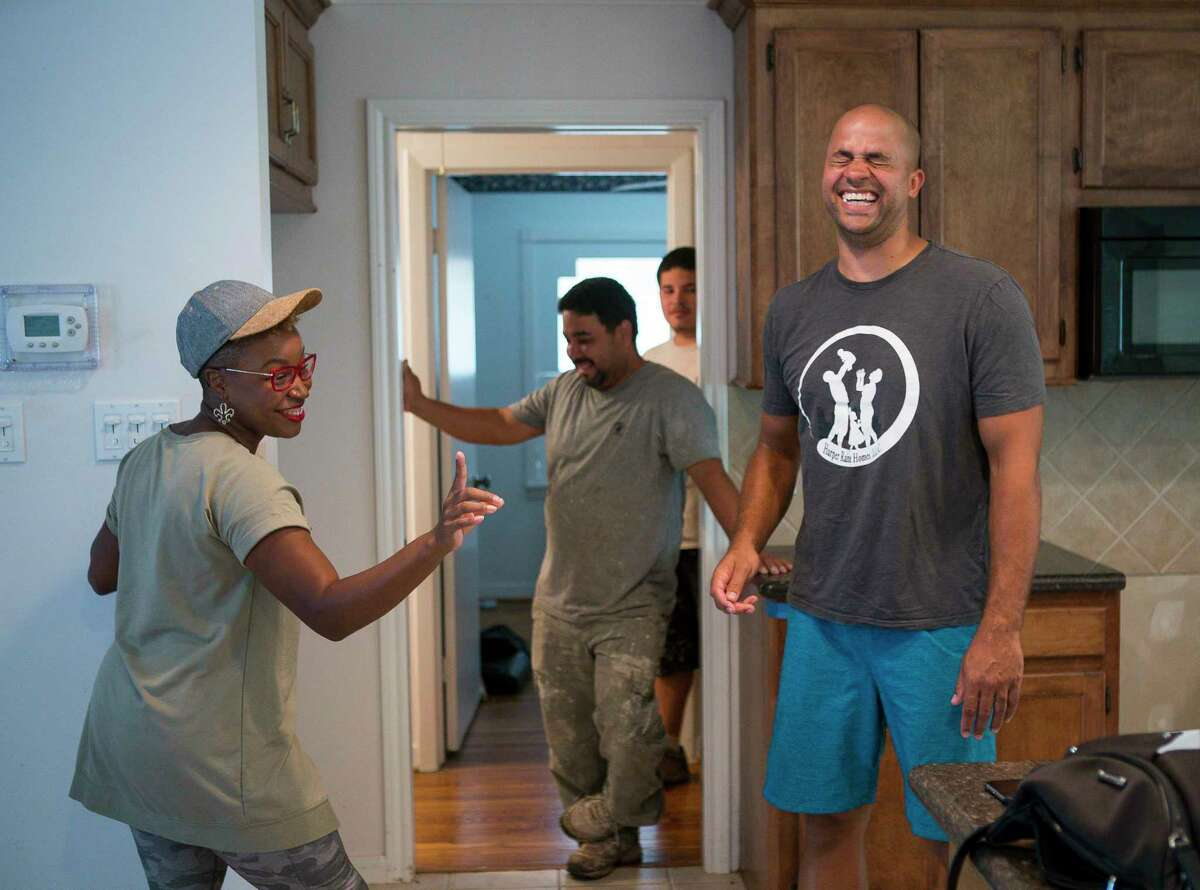 """Mary and Jon Tjon-Joe-Pin laugh over a disagreement as they walk through plans with their contractors for a home they are flipping in the Oak Forest neighborhood, Tuesday, July 9, 2019. The couple have a new show called """"Going for Sold"""" debuting in August on HGTV about flipping Houston real estate."""
