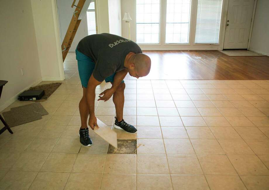 """Jon Tjon-Joe-Pin looks under the existing tile in a home he is flipping with his wife, Mary, in the Oak Forest neighborhood, Tuesday, July 9, 2019. The couple have a new show called """"Going for Sold"""" debuting in August on HGTV about flipping Houston real estate. But even as flipping grows in popularity, returns have shrunk. Photo: Mark Mulligan, Houston Chronicle / Staff Photographer / © 2019 Mark Mulligan / Houston Chronicle"""