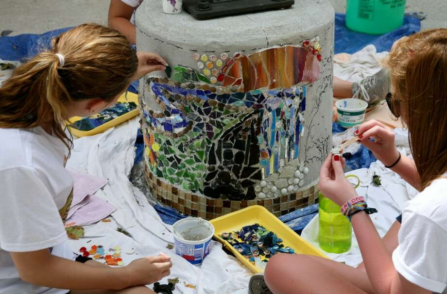 LASTING WORK: Artworks campers add glass pieces to a mosaic in Pocket Park. The City of Big Rapids and the Arts Council of Greater Grand Rapids contributed funds for the project.