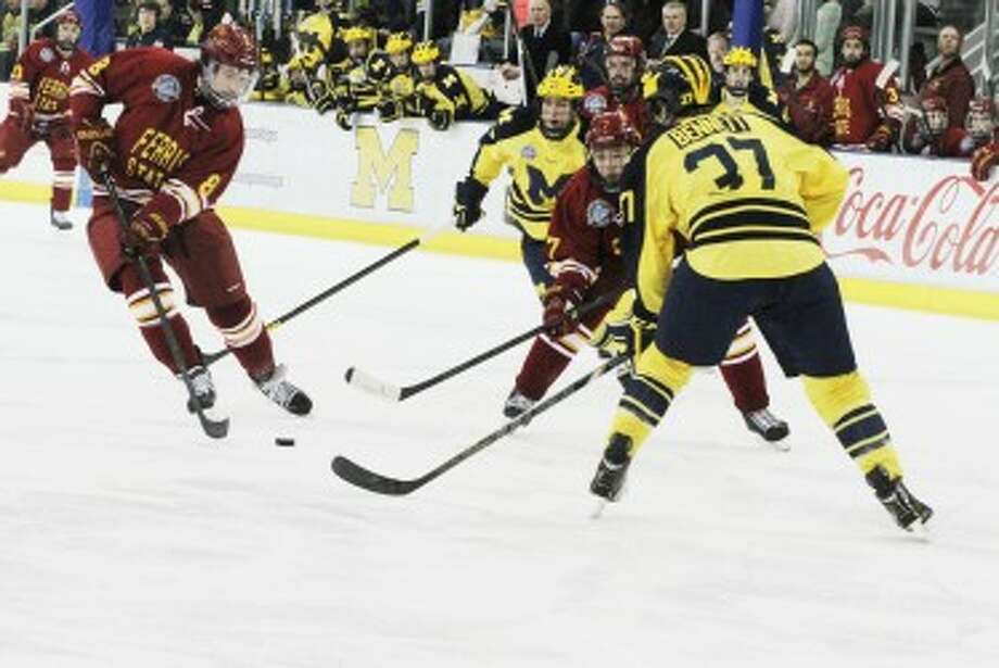 CCHA FINALE: Ferris State forward Cory Kane (left) looks to put a shot on net against Michigan during Saturday's hockey action at Yost Ice Arena. (Pioneer photo/Martin Slagter)